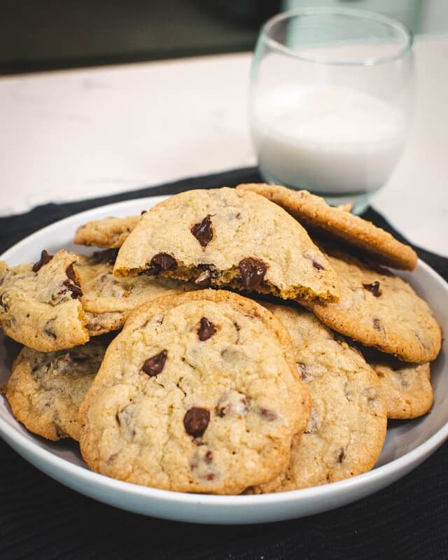 one of the best sweet treats, chocolate-chip cookies placed in a white plate with half glass of milk in the background